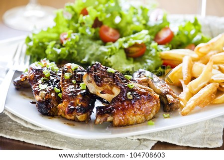 Photograph of some tasty barbecue chicken wings with salad