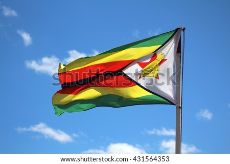 Photograph of the flag of Zimbabwe fluttering in the wind against a blue sky on a sunny day.