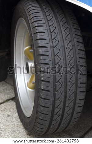 Photograph of the wheel of a car on the street. Stock photography.
