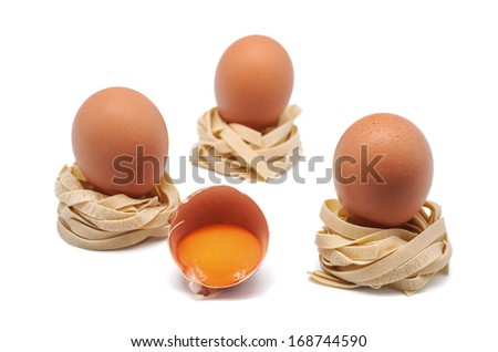photograph of three eggs and half with several nests of pasta