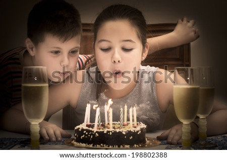 photograph of two children blowing out candles on her birthday cake - stock photo