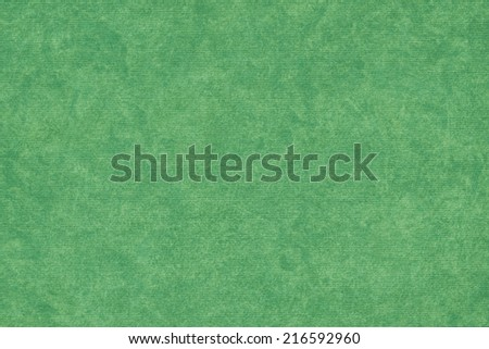 Photograph of vivid, saturated Kelly Green recycle striped paper, extra coarse grain, mottled grunge texture sample. - stock photo
