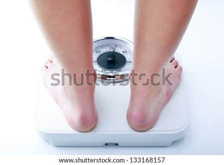 Photograph showing a woman on a bathroom scale close-up