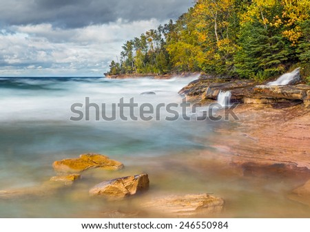 Photographed with a long exposure, waves crash on the rocky coast of Miner's Beach at Upper Peninsula Michigan's Pictured Rocks National Lakeshore as Elliot Falls spills into Lake Superior. - stock photo
