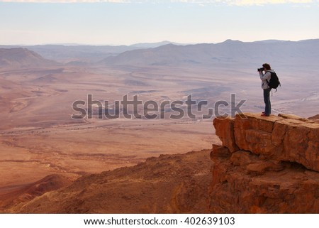 Photographer admiring the scenery, the views from the top of the cliff