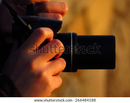 photographer and his zoom camera at sunset - stock photo