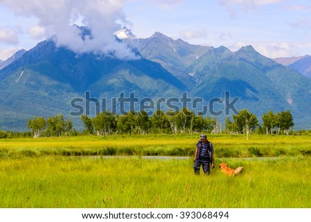 photographer and the dog go on the field across the mountains