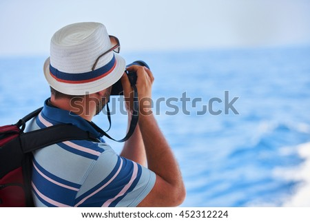 photographer and traveler with the backpack taking pictures outdoors       - stock photo
