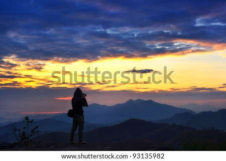 Photographer at mountain landscape at sun rise time