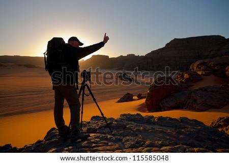 Photographer at sunset in the desert - stock photo