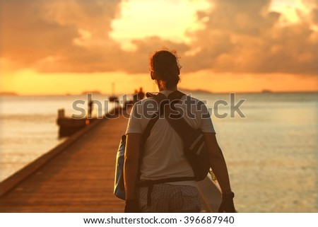 photographer at sunset is on the pier, a boat is going to sail to the core, to remove the sunset - stock photo