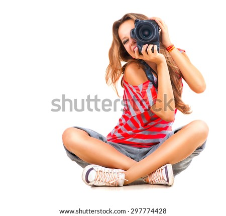 Photographer. Beauty Teenage Girl taking photo, sitting and Smiling. Beautiful Teen Girl with professional photo camera (unrecognizable). Isolated on a White Background. Teenager  - stock photo
