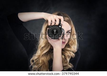 Photographer blond woman holding camera over dark background. - stock photo