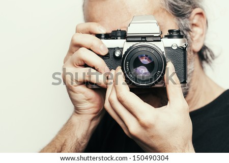 Photographer. Close up portrait of man holding vintage camera. - stock photo