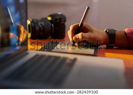 Photographer drawing and retouching image on laptop computer, using a digital tablet and stylus pen. Closeup of man's hand with dslr camera in background. Copy space in foreground - stock photo