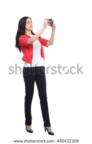 Photographer, fashion, holidays, journey, trip concept - the portrait of young adult standing fashion slender woman with camera wearing on red jacket & black trousers   isolated over white background