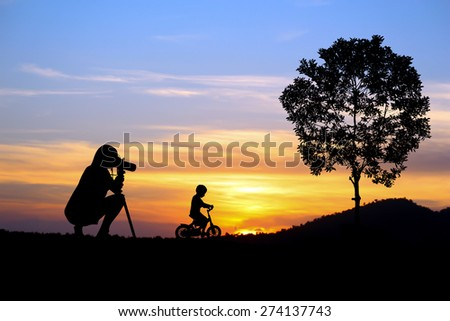 Photographer girl with little boy at orange sunset.