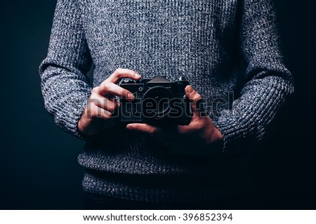 Photographer holding his finger on vintage camera shutter release button ready to shoot new photo