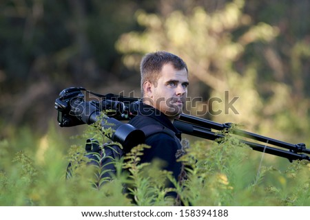 Photographer holds photo camera and stand on his shoulder in forest - stock photo
