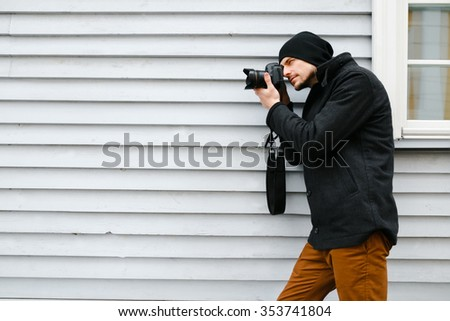 Photographer in a dark coat and hat takes pictures on his camera, side view
