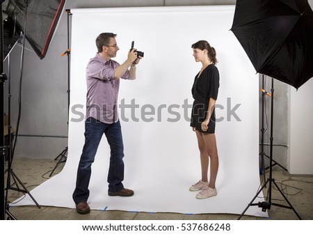 Photographer in a studio demonstrating how to light a model and take photos.  He is using softboxes with a white background.