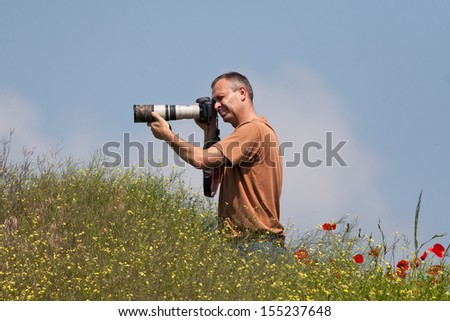 Photographer in action in poppy field - stock photo