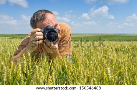 Photographer in action in the wheat field - stock photo
