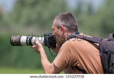 Photographer in action with  telephoto lens