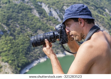 Photographer in action with telephoto lens. Shallow DOF.