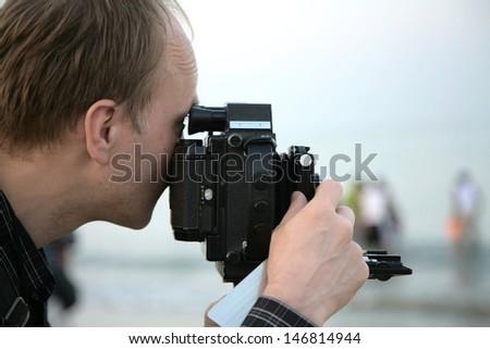 Photographer in beach, India - stock photo