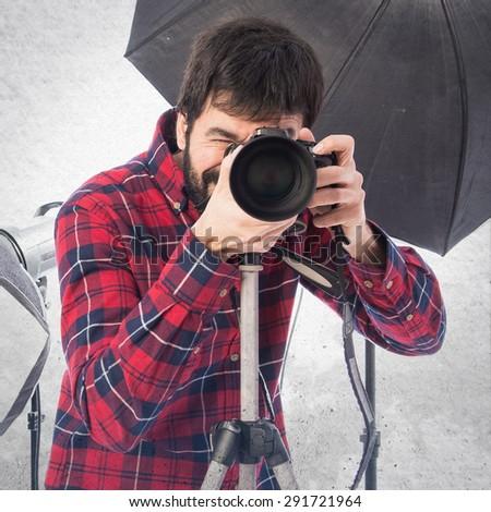 Photographer in his studio over grey background - stock photo