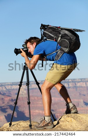 Photographer in Landscape nature in Grand Canyon taking picture photos with SLR camera and tripod during hike on south rim. Young man hiker enjoying landscape in Grand Canyon, Arizona, USA. - stock photo
