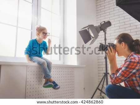 Photographer in motion. Young woman photographer and child girl having fun at the photo session. - stock photo