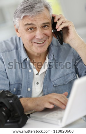 Photographer in office talking to client on the phone - stock photo