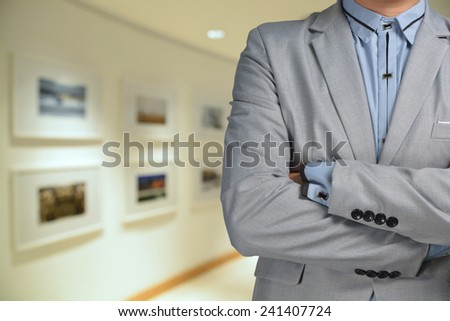 Photographer in Suit standing in front of Blur Background of image gallery or exhibition hall - stock photo