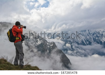 photographer in the mountains taking a picture of the landscape