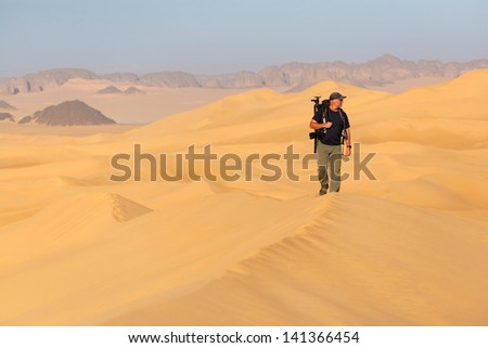 Photographer in the Sahara desert, close to the city of Djanet on the border with Libya - stock photo