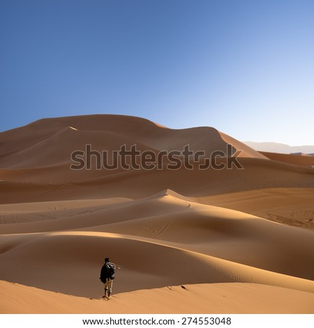 photographer in the sahara desert, morocco - stock photo