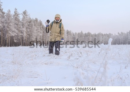 Photographer in winter forest