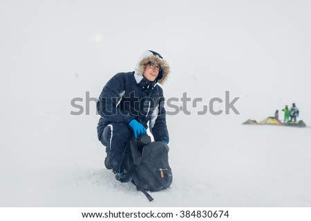 Photographer is going to take pictures on the river bank in winter - stock photo