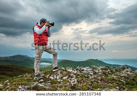 Photographer is taking a picture of  landscape in mountains - stock photo