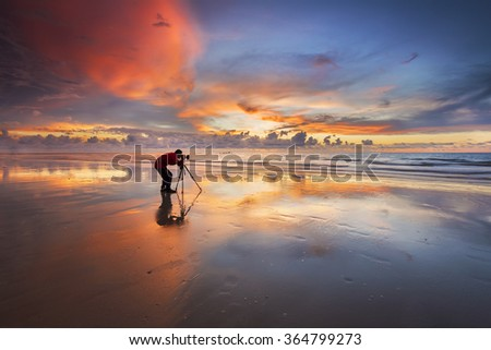 Photographer is taking a picture of sunset at beach