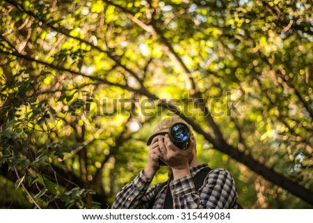 Photographer man in green forest with sun light bright background Empty copy space for inscription Professional male in autumn park during a photo shoot in outdoor - stock photo