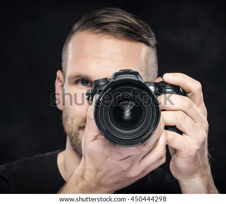 Photographer man with camera on darck background. Focus on camera.