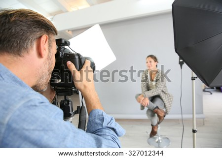 Photographer on a shooting day in studio with model - stock photo