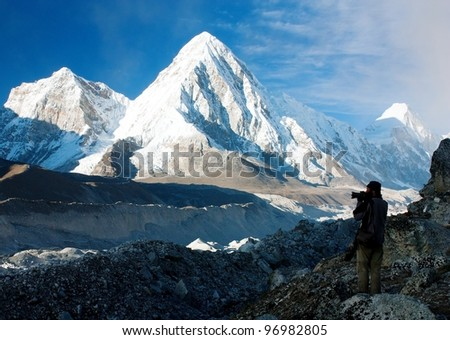 photographer on mountains - hiking in Nepal - way to everest base camp - stock photo