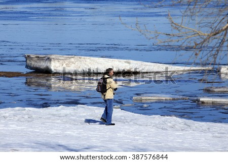 photographer on the river in early spring flood in a sunny day - stock photo