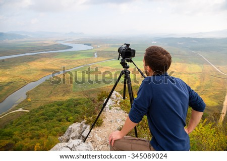 Photographer on top of a mountain landscape on the camera shoots. - stock photo