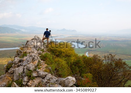 Photographer on top of a mountain landscape on the camera shoots.