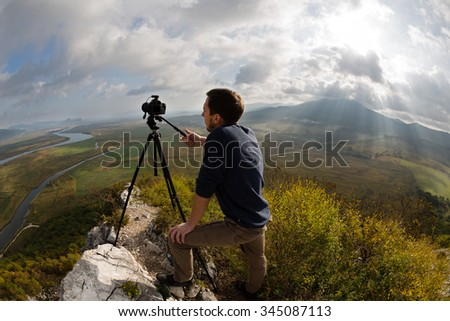 Photographer on top of the mountain. Sun rays make their way through the clouds. Taken with a fisheye lens.